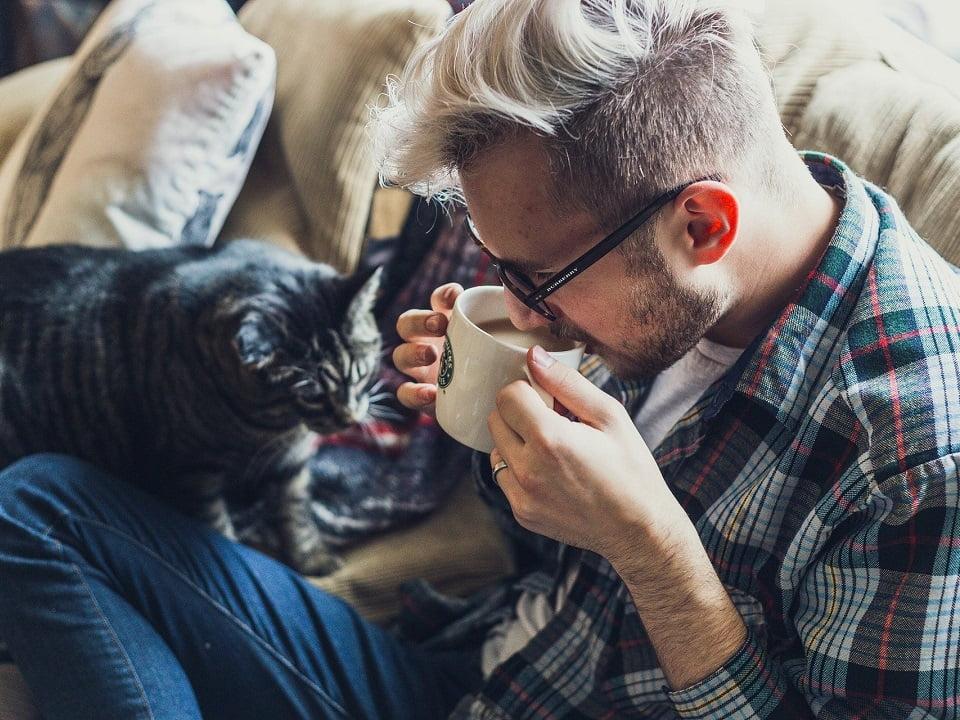 mies juo kahvia kotona kissan kanssa